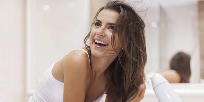 femme se séchant les cheveux